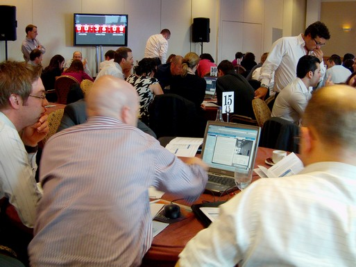Participants at a team-building event using a simulation on laptops with a countdown timer on screen