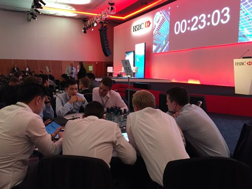 Graduate recruits around a conference table taking part in a sim about risk in banking