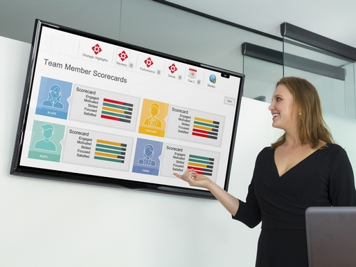 Facilitator pointing at team member scorecards on large screen