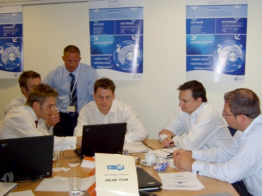 Photo of team members around a laptop during a workshop-delivered simulation