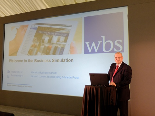 Facilitator on stage for WBS business simulation standing in front of projector screen