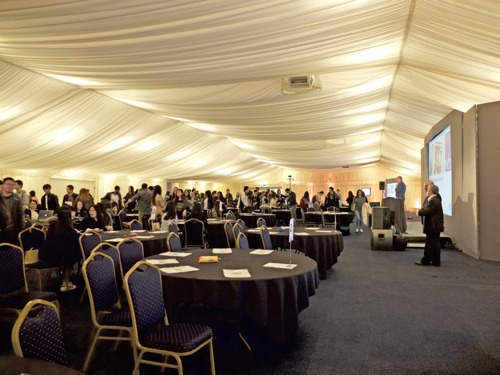 Business students in huge marquee receiving simulation results